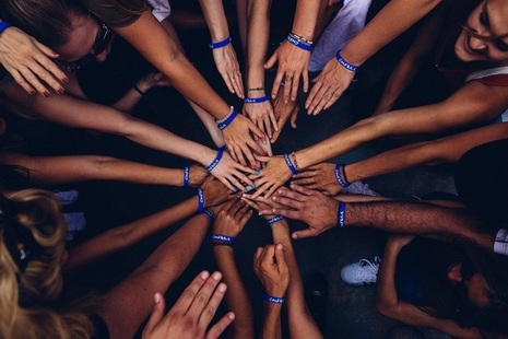 Hands representing diverse communitties touching in order to make a circle.