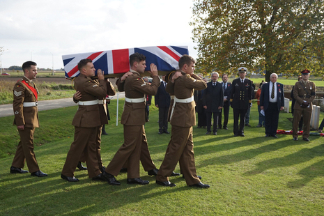 The bearer party carry the coffin of the unknown soldiers into New Irish Farm Cemetery.