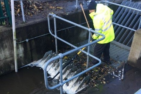 Environment Agency officer clearing debris from a screen
