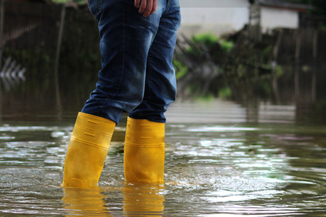 Person with yellow wellies standing in a flood