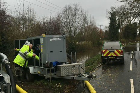 An Environment Agency officer operating a water pump beside a road with an EA vehicle in the background
