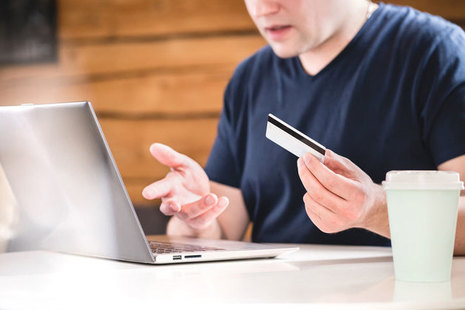 Person with laptop holding a credit card