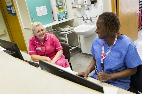 Two nurses talking and smiling at a reception desk