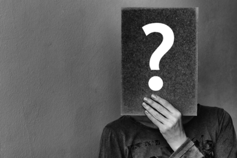 A person holding a card in front of their face with a question mark on it.