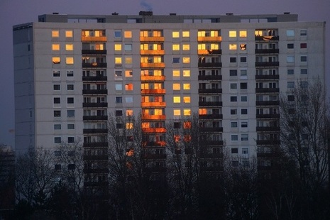 Apartment block on winter's evening with trees in foreground