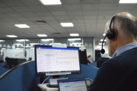 Man with telephone headset looking at computer screen