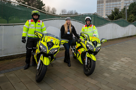 2 women and 1 man standing by 2 motorbikes outside the Driver and Vehicle Licensing Agency