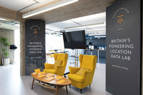 Two chairs and a desk in front of a screen and flanked by banners at the Geovation hub in London.