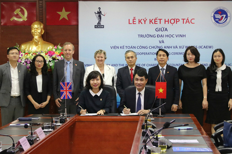 Minister Heather Wheeler with Ambassador Gareth Ward and others at Vinh University as 2 people sign documents