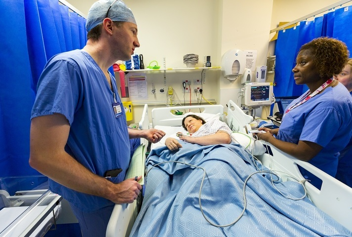 Surgeon and medical staff talking to patient in bed