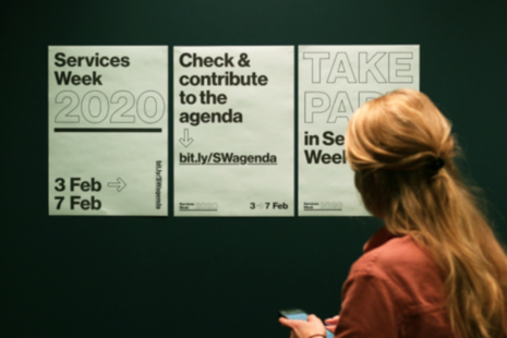 Woman looking at services week 2020 posters.