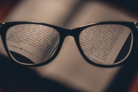 Spectacles hovering over book