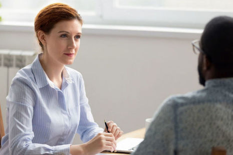 Image of a woman sitting at desk conducting an interview. Getty Images copyright, all rights reserved.