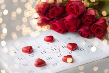 A calendar with 14 February circled in a love heart next to a bouquet of roses and heart shaped chocolates in red foil.