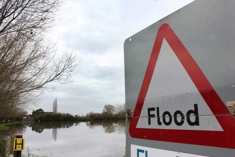 Flood sign overlooking flooded land in a rural area