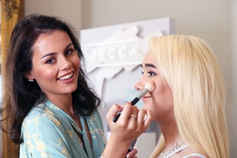 A photo of a lady smiling at the camera whilst doing another lady's makeup.