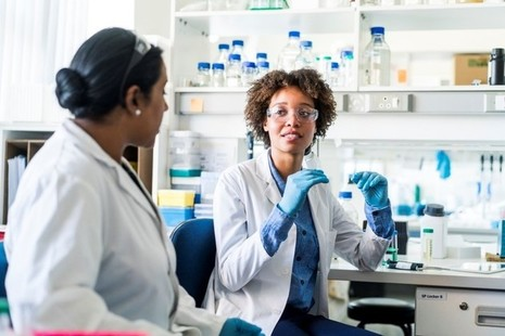 2 female scientists in a lab having a conversation