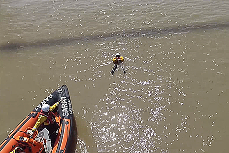 Aerial view of rescue boat approaching casualty on the water