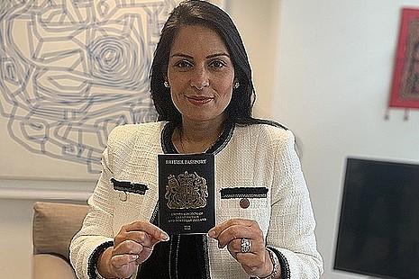 Home Secretary, Priti Patel, holding a blue passport