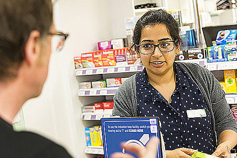 A pharmacist and a man talk over the counter in a pharmacy