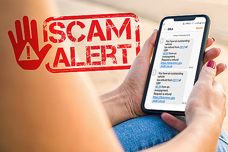 Hands holding a mobile phone with a scam text message on it