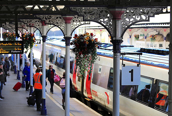 Rail station platform in summer, with passengers, a train and hanging baskets with flowers.