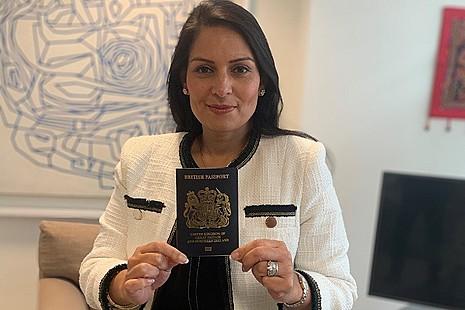 The Home Secretary holding a blue passport.
