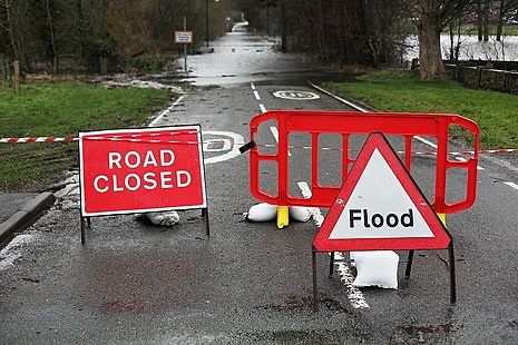 Flood and road closed signs on a flooded road