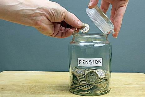 Hand putting coins in jar marked pensions