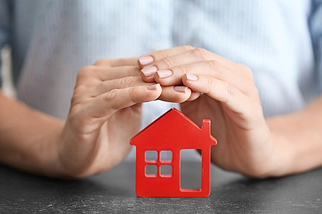 Photo of hands over house