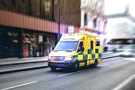 ambulancd driving down a street