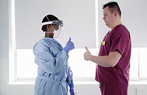 Two professionals in a clinical setting wearing PPE