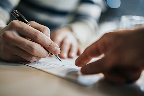two hands, one holding a pen, pointing at a document
