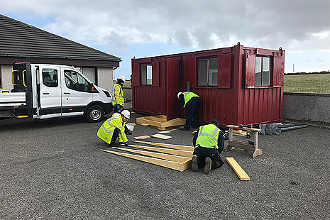 Workers installing a welfare cabin at a local medical practice