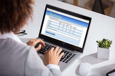 Woman filling in survey on laptop