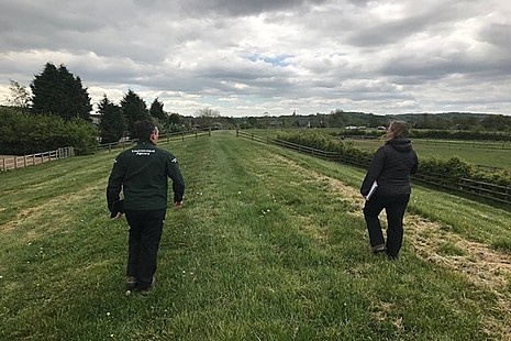 Two Environment Agency staff in a field socially distancing.