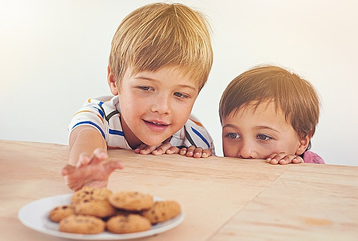 Children reaching for biscuits