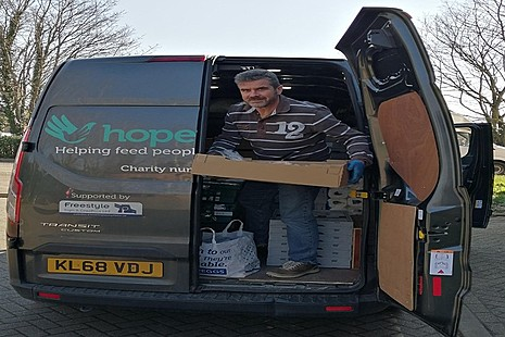 Volunteer carrying crates out of the Hope Enterprises van