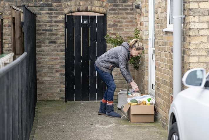 A woman leaving a box of groceries outside a front door
