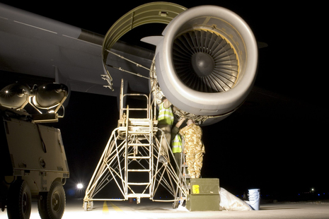 RAF technicians carrying out some late night repairs to an engine on a C-17 aircraft.