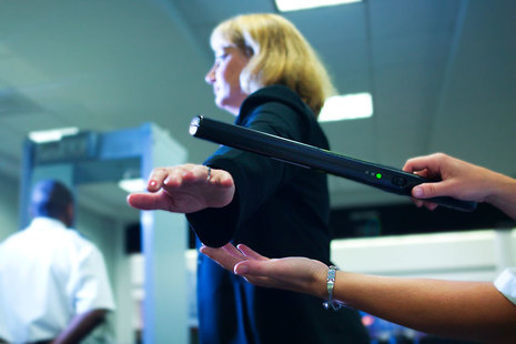 Woman being scanned with a security wand entering a building