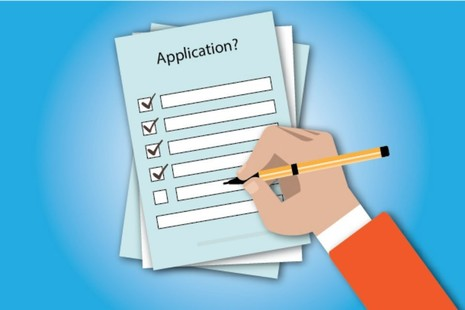 picture of hand holding a pen completing an application
