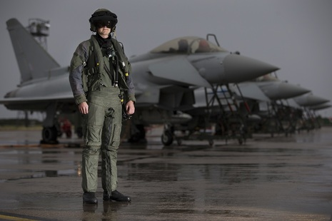 A pilot from 6 Squadron, RAF Lossiemouth, in front of a line of Typhoon aircraft in full flying attire.