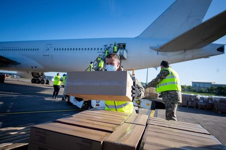 Soldiers unloading a PPE shipment from an aircraft