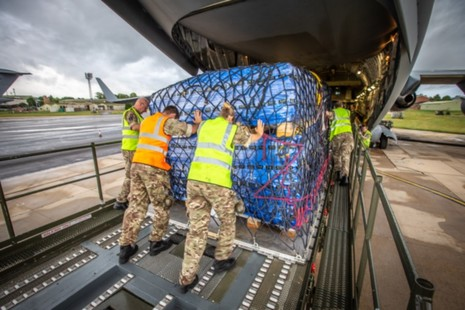 Personnel load cargo forming part of a World Food Programme field hospital onto an RAF C-17 aircraft at RAF Brize Norton.