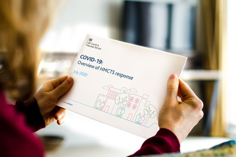 Image of someone holding the recovery plan document sitting by desk