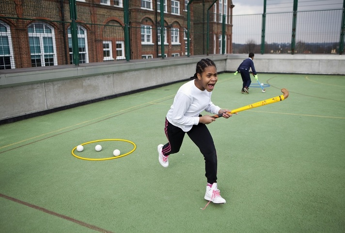 A girl playing hockey in a school playground