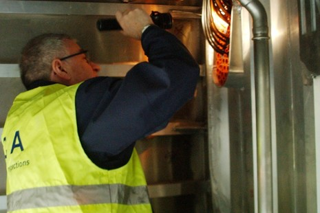 Surveyor inspecting light fitting