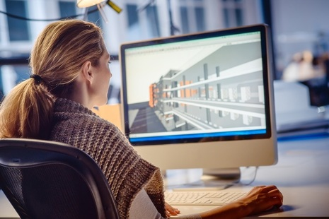 Woman in front of plan on computer screen