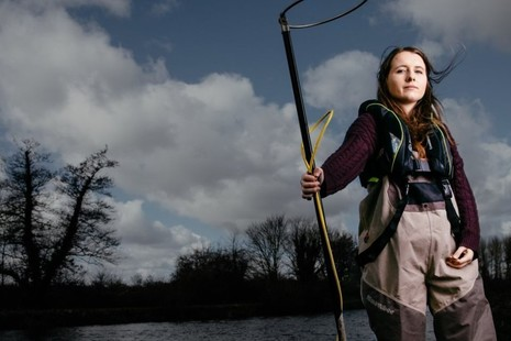 A female Environment Agency employee stands with an electro-fishing rod by a lake